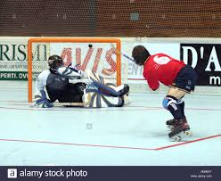 two roller hockey players one shooting at goal at mens hardball