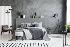 grau sessel und hocker in der nähe bett mit kopfteil im schlafzimmer inter foto bialasiewicz auf envato elements