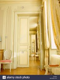 Silk Drapes On Tall Windows In Opulent French Chateau Dining Room With Double Doors Open To Drawing