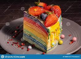 ein stück regenbogenkuchen mit erdbeeren und heidelbeeren