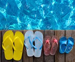 Brightly Colored Flip Flops Of The Family On Wooden Background Near Pool Summer