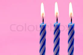 Three blue and white birthday candles on pink background Stock