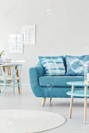 gemusterte kissen auf türkis sofa in hellen wohnzimmer interieur mit runden teppich und plakaten an der wand