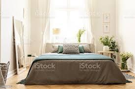 beige grün und grau schlafzimmer innenraum in ein mietshaus mit einem bett gegen einen sonnigen fenster haus und trauben wildblumen echtes foto