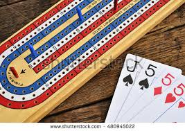 A Top View Image Of Wooden Cribbage Board With Playing Cards On Table