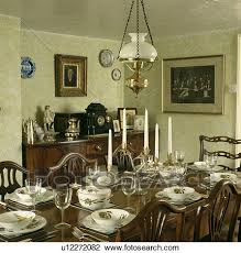 Victorian Style Lamp Over Antique Table With Fruit Patterned Crockery In Country Dining Room