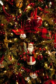 A Christmas Tree Full Of Red And White Jingle Bells Plaid Ribbons
