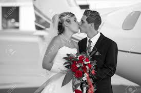 Black And White Wedding Photo With Colored Bunch Of Red Roses While Holding The Bouquet