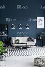 weißen sofa couchtisch uhren an der grauen wand und gestreiften teppich in einem modernen wohnzimmer interieur stockfoto und mehr bilder