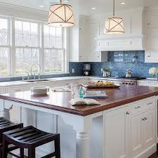white kitchen cabinets with blue subway tiles transitional