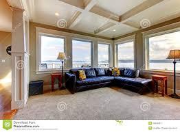 wohnzimmer wih viele großen fenster und blaues sofa