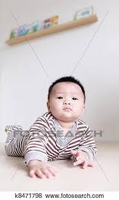 süße babys krabbelnd auf wohnzimmer boden stock foto