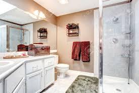 beige und weiß bad mit glastür dusche fliesenboden und grün weichen teppich mit burgunder handtuch antike truhe und wandregal dekoriert