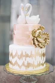 A Two Tier Blush And Gold Wedding Cake With Swan Topper By