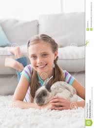 lächelndes mädchen mit dem kaninchen das auf wolldecke im