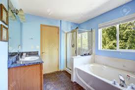 badezimmer interieur mit blauen wänden und rost fliesenboden weiß badewanne abgeschirmt dusche und schrank mit spiegel