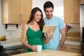 mann und frau betrachten familienfotos in der modernen küche