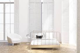 gehobenes schlafzimmer mit hohen fenstern einem holzboden weißen wänden und einem weißen bett in der mitte mit einem sessel daneben seitenansicht