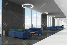 Office Waiting Area With Dark Blue Sofas Coffee Tables Round Ceiling Lamps And Loft