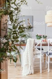 decke auf weißen stuhl am tisch im esszimmer interieur mit blumen und rattan le echtes foto stockfoto und mehr bilder behaglich