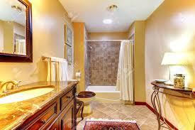 goldene schönes badezimmer mit braunen fliesen und holz schrank