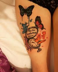 Lovely Butterflies Memorial Tattoo On Girl Thigh