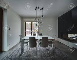 zimmer mit hellen wänden auf dem boden befinden sich graue fliesen und ein grauer teppich auf dem teppich steht tisch mit milchglasplatte und