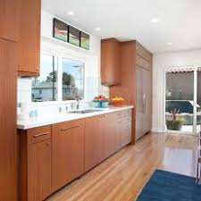 Midcentury Modern Kitchen With Woodgrain Cabinetry Around White Countertop Sink Window And Stainless Steel Appliances
