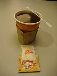 A Cup Of Coffee With Sachet Sugar And Plastic Mate Non Dairy Creamer