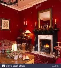 rote wohnzimmer mit offenem feuer für weihnachten dekoriert