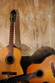 Two Old Acoustic Guitars Against Grunge Aged Surface Stock Photo