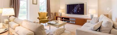 stilvolles wohnzimmer mit zwei sofas couchtisch und bequemen grünen sessel