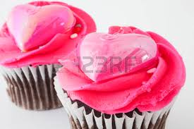 Two chocolate cupcakes with pink frosting and hearts on top photo
