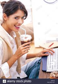 A Woman Is Drinking An Iced Coffee In Take Out Cup While Working On Her Computer