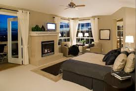 Master Bedroom With French Doors And A Large Stone Fireplace