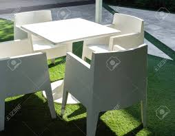 White Modern Garden Dining Table And Four Chairs On Green Yard... Adams Manufacturing Quikfold White Resin Plastic Outdoor Lawn Chair Semco Plastics Patio Rocking Semw 5 Pc Wicker Set 4 Side Chairs And Square Ding Table Gray For Covers Sets Tempered Round 4piece Honey Brown Steel Fniture Loveseat 2 Sku Northlight Cw3915 Extraordinary Clearance Black Bar Rattan Small Bistro Pa Astonishing And Metal Suncast Elements Lounge With Storage In
