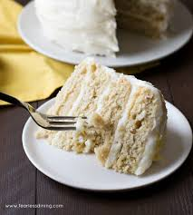 A slice of Gluten Free Lemon Layer Cake on a plate with a fork taking out