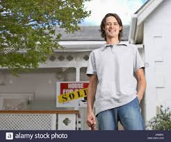 Man With Keys Standing In Front Of House Sold Sign