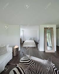 wohnzimmer mit schlafzimmerblick leder zebra auf dem boden weiße wände