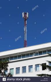 cell phone red and white antenna tower situated on top of white office building with