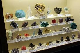 Mixed Case Of Mineral Specimens Displayed On Traditional Fabric Covered Risers