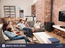familie sitzen auf sofa in offenes wohnzimmer vor dem