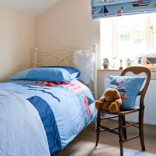 Nautical Themed Young Boys Bedroom With Blue Bed Linen And Wooden Chair