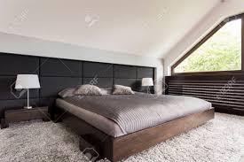 elegantes großes bett in einem dunklen rahmen in einem schlafzimmer im dachgeschoss