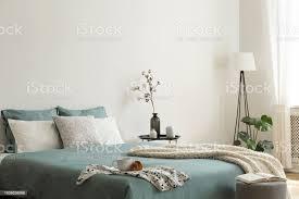 schlafzimmer innenraum mit salbei grünweiße bettwäsche und kissen und eine decke schwarze metalltisch mit vasen neben dem bett eine le in der ecke