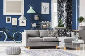 großes wohnzimmer mit blauen wänden grauem sofa und vielen modischen accessoires