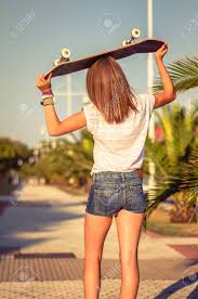 back view of beautiful young with short shorts and skateboard