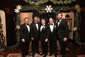 Groom With Dad And Groomsmen In Front Of Christmas Decorations