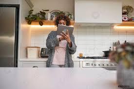 foto auf lager reife afrikanisch amerikanische frau im schlafanzug zu hause in der küche die digitale tablette anschaut