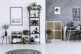 plakat auf weißer wand über anlagen im geräumigen wohnzimmerinnenraum mit arbeitsbereich gegen graue wand